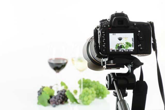 A camera taking a picture of wine and grapes in a studio.