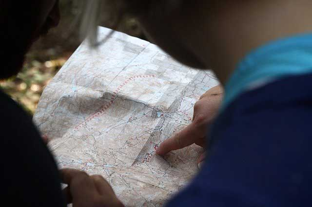 A woman pointing to a location on a map.