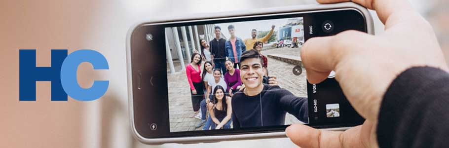 Friends take a group photo on their phone.