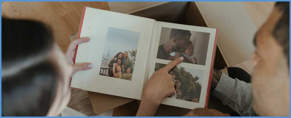 Two people look at a photo album.