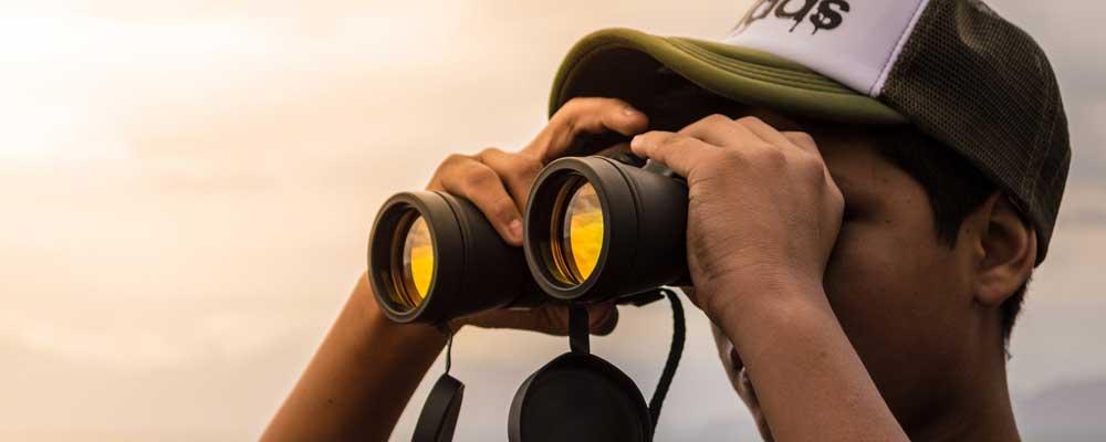Man using a pair of binoculars.