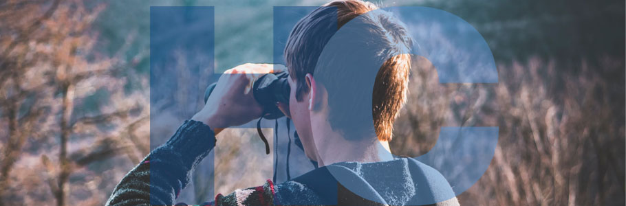 Man using binoculars in the countryside.