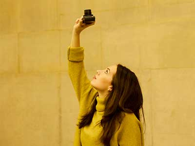 Woman pointing a camera upwards