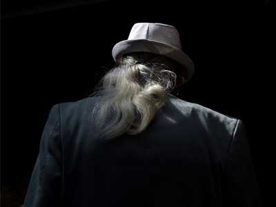 Long grey haired man with hat walking away