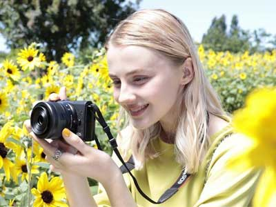 Woman in a field shooting the Canon EOS M200