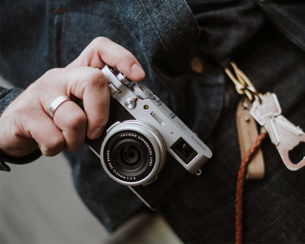 Person with finger over the shutter of the Fujifilm X100V.